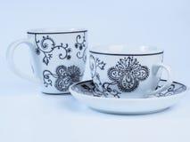 Dois copos de chá decorados com os projetos isolados no fundo branco Fotos de Stock Royalty Free