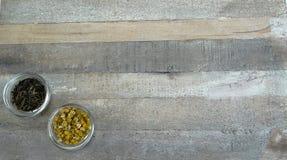 Dois copos de chá no vidro com chá preto e chá de camomila no fundo de madeira natural foto de stock royalty free