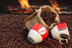 Dois copos de feijões do café e de café em um fundo do fogo Fotografia de Stock Royalty Free
