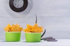 Dois copos de papel com nachos em um fundo claro imagem de stock
