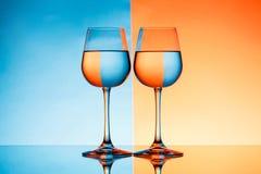Dois copos de vinho com água sobre o fundo azul e alaranjado Imagem de Stock Royalty Free