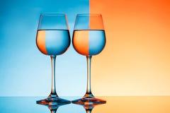 Dois copos de vinho com água sobre o fundo azul e alaranjado Fotografia de Stock Royalty Free