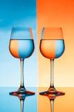 Dois copos de vinho com água sobre o fundo azul e alaranjado Foto de Stock