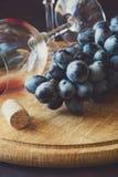 Dois copos de vinho com vinho tinto e uvas decoraram as folhas da videira Foto de Stock