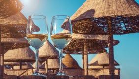 Dois copos de vinho do vinho branco Praia ensolarada com palmas e guarda-chuvas Foto de Stock Royalty Free