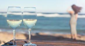 Dois copos de vinho do vinho branco sobre o fundo do mar Fotografia de Stock