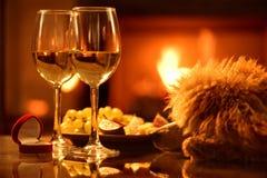 Dois copos de vinho do vinho com a caixa vermelha com anel de noivado sobre o fundo da chaminé Fotos de Stock