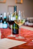 Dois copos de vinho por uma folha do gosto e por uma garrafa de vinho Fotos de Stock Royalty Free