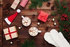 Dois copos do cacau ou do chocolate quente com marshmallow, presentes, os mitenes brancos, a decoração do Natal e a árvore de abe Foto de Stock Royalty Free