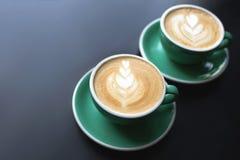 Dois copos do café do cappuccino ou do latte com leite na tabela da casca Espuma bonita foto de stock royalty free