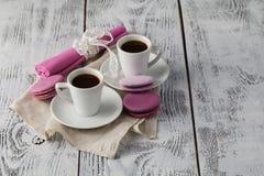 Dois copos do café com os bolinhos de amêndoa na tabela rústica Fotografia de Stock Royalty Free