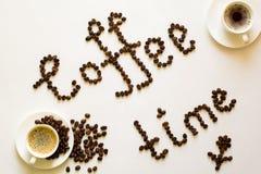Dois copos do café e do tempo do café text dos feijões na tabela branca Foto de Stock