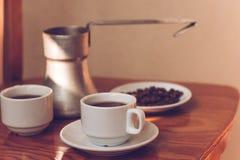 Dois copos do café preto e do cezve Fotos de Stock Royalty Free