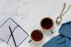 Dois copos do café preto e de um caderno em um mármore surgem Fotografia de Stock