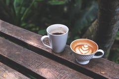 Dois copos do café preto e do latte com arte do latte do coração no banco de madeira no fundo verde da natureza Imagens de Stock Royalty Free