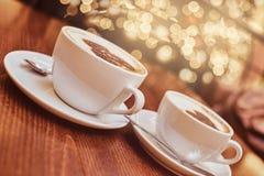 Dois copos do café quente com arte na tabela de madeira em uma cafetaria, fundo do borrão com efeito do bokeh fotografia de stock royalty free