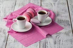 Dois copos do café do café com os bolinhos de amêndoa no fundo cor-de-rosa Fotografia de Stock Royalty Free