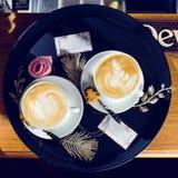 Dois copos do cappuccino na bandeja e dos cartões com copyspace f Fotografia de Stock