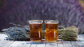 Dois copos do chá e de um ramalhete da alfazema em um fundo de um b Imagens de Stock
