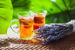 Dois copos do chá e de um ramalhete da alfazema em um fundo de um b Foto de Stock