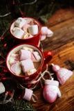 Dois copos do chocolate quente com marshmallows e bastões de doces e de alamedas vermelhas do Natal em um fundo de madeira escuro foto de stock royalty free