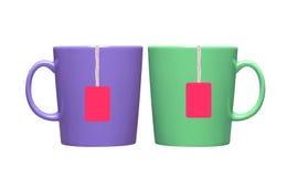 Dois copos e saquinhos de chá com a etiqueta alaranjada isolada no branco imagem de stock