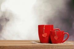Dois copos vermelhos na tabela de madeira Imagens de Stock