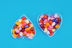 Dois corações com os doces no fundo azul imagem de stock royalty free