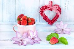 Dois corações da tela com morangos maduras em um presente cerâmico cor-de-rosa do copo para o dia do ` s do Valentim em um fundo  Fotografia de Stock