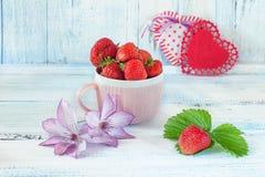 Dois corações da tela com morangos maduras em um presente cerâmico cor-de-rosa do copo para o dia do ` s do Valentim em um fundo  Fotos de Stock