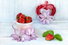 Dois corações da tela com morangos maduras em um presente cerâmico cor-de-rosa do copo para o dia do ` s do Valentim em um fundo  Fotos de Stock Royalty Free