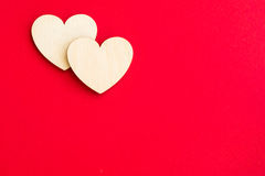 Dois corações de madeira em um fundo vermelho brilhante Fotos de Stock Royalty Free