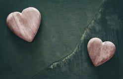 Dois corações de madeira estilizados retros em fundo de pedra rachado Fotos de Stock Royalty Free