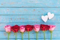 Dois corações do amor com as rosas cor-de-rosa e vermelhas românticas na luz - madeira azul para o dia ou o casamento de Valentim Foto de Stock