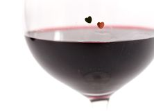 Dois corações em um vidro com vinho tinto no fundo branco imagem de stock
