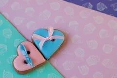 Dois corações feitos da configuração dos bolos de mel em aumentaram, esverdeiam, fundo roxo Vista superior Fotos de Stock