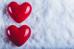 Dois corações lustrosos vermelhos em um fundo branco gelado da neve Amor e conceito do Valentim do St Imagem de Stock Royalty Free