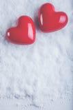 Dois corações lustrosos vermelhos em um fundo branco gelado da neve Amor e conceito do Valentim do St Imagens de Stock Royalty Free
