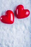 Dois corações lustrosos vermelhos em um fundo branco gelado da neve Amor e conceito do Valentim do St Fotografia de Stock Royalty Free