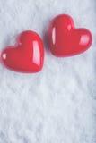 Dois corações lustrosos vermelhos em um fundo branco gelado da neve Amor e conceito do Valentim do St Foto de Stock Royalty Free