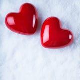 Dois corações lustrosos vermelhos em um fundo branco gelado da neve Amor e conceito do Valentim do St Fotos de Stock