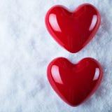 Dois corações lustrosos vermelhos em um fundo branco gelado da neve Amor e conceito do Valentim do St Imagens de Stock