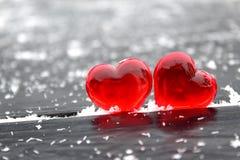 Dois corações plásticos vermelhos em um fundo preto enchido com flocos de neve brancos imagens de stock