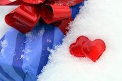 Dois corações plásticos vermelhos na neve com um presente fotos de stock royalty free