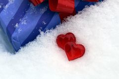 Dois corações plásticos vermelhos na neve com um presente foto de stock royalty free