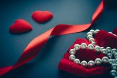 Dois corações vermelhos brilhantes com fitas e as pérolas vermelhas Fotografia de Stock