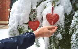 Dois corações vermelhos de matéria têxtil e mãos do homem no fundo nevado pesado do ramo do abeto, perto da casa do tijolo vermel imagens de stock royalty free