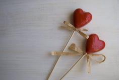 Dois corações vermelhos em um fundo de madeira branco Foto de Stock