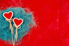 Dois corações vermelhos em um fundo vermelho, fundo brilhante foto de stock