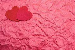 Dois corações vermelhos em um fundo vermelho esmagaram o amor do Valentim do St fotografia de stock royalty free